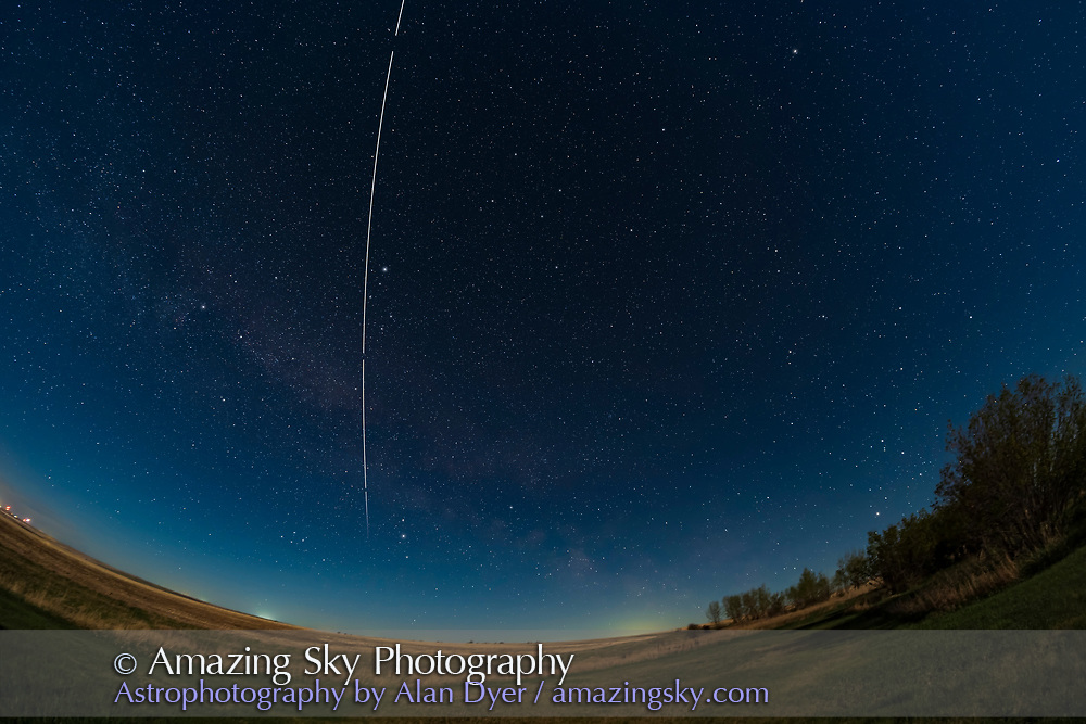 An overhead pass of the International Space Station on May 18, 2021, with the 6-day waxing Moon providing the illumination. The Milky Way in Cygnus runs diagonally across the east at left, with Scorpius rising in the southeast at right.<br /> <br /> This is a stack of 4 x 1-minute tracked exposures at f/2.8, and ISO 800 with the Canon EOS Ra. I did not fill in the gaps created by the 1 second interval between exposures. The ground is masked to come from one of the exposures, the first, to minimize blurring from the star tracker motion following the sky. Taken from home as part of testing the TTArtisan 11mm fish-eye lens.
