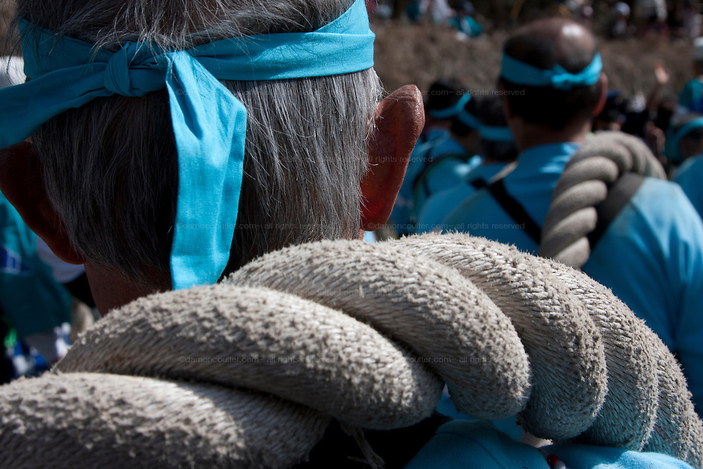 Festival supporters, wearing blue, carrying ropes that are usewd to draglarge pine tree trunks down a hill during the Onbashira matsuri which takes place every seven years in the town of Suwa, Nagano. Japan. April 10th 2010