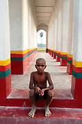 Bihar India March 2011. Young boy sitting on step of Hindu temple.