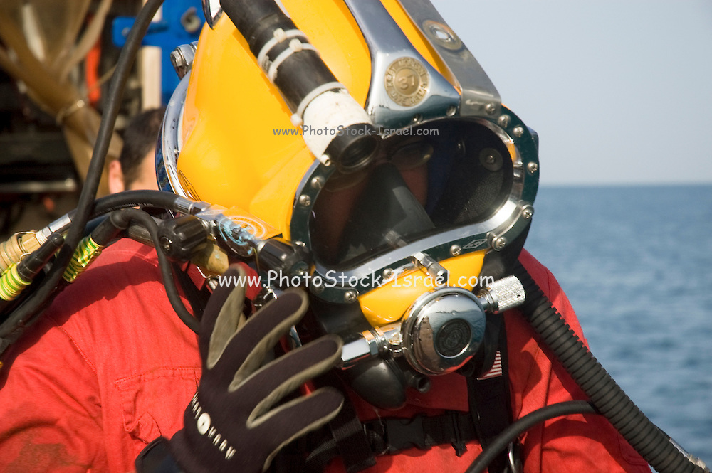 Commercial diver entering the Mediterranean sea. Cables from the surface are supplying electrical power for the lights, and allowing communication with the surface. The diver is using a helmet connected to an air supply on his back. close up of the helmet as worn by the diver.Photographed of the shore of Hadera, Israel