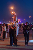 Carrying the flame that will light the fires for the fire conclave dancers.