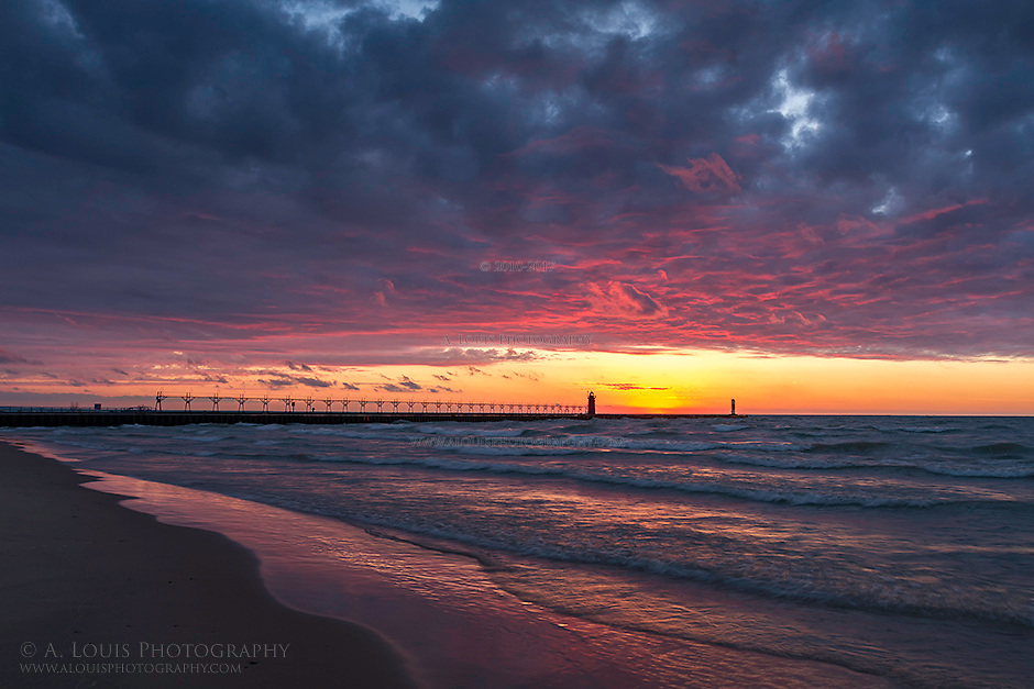 The setting sun casts its fiery light on the clouds above the South Haven lighthouse.