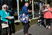 Man eating his lunch outside a fish and chip shop, with his Dachshund 'Sausage' in his bag. Whitby seems to have a particular affinity with dog owners, as at every turn there seems to be a different breed. Whitby is a seaside town, port in the county of North Yorkshire, originally the North Riding. Situated on the east coast at the mouth of the River Esk. Tourism started in Whitby during the Georgian period and developed. Its attraction as a tourist destination is enhanced by its proximity to the high ground of the North York Moors, its famous abbey, and by its association with the horror novel Dracula. Yorkshire, England, UK.