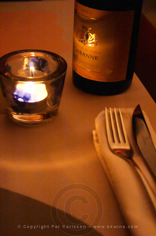 Inside the restaurant Le Mornet  A candle, a bottle of Cairanne, linen napkin and knife and fork.  Avignon, Vaucluse, Provence, Alpes Cote d Azur, France, Europe