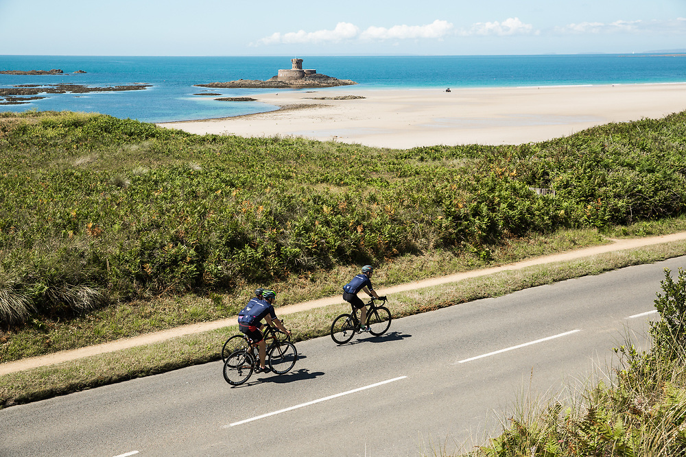 People cycling along St Ouen's Bay with the landmark La Rocco Tower and the beach in the background on a summer day in Jersey, Channel Islands