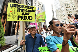 Anti-Trump protestors holds signs up during a pro-migration rally near Trump Tower during President Donald Trump's first stay in New York City since taking office, New York, NY, on August 15, 2017. (Photo by Anthony Behar)