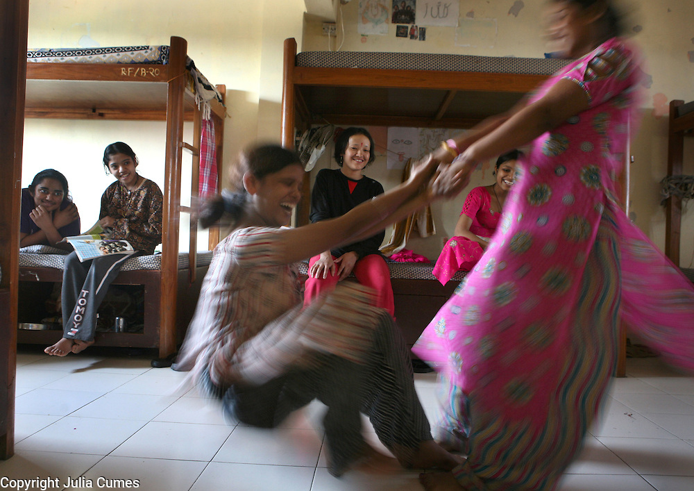 Young girls enjoy a spinning game in their hostel at the Rescue Foundation, a non-governmental organization founded to rescue young girls from brothels in and around Mumbai, India. The Rescue Foundation houses over 50 rescued girls at a time. Most are under the age of 18 . Many of the girls suffer from some form of post-traumatic stress syndrome. One girl doesn't speak while another tried to commit suicide by setting herself on fire while still at a brothel.