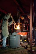 Klokkengieter Simon Laudy roert in de bak met brons van 1100 graden. Op de Domplein in Utrecht wordt een klok gegoten dat door de Utrechtse Klokkenluidersgilde wordt geschonken aan het  Academiegebouw van de Universiteit Utrecht ter gelegenheid van hun 375 jarig bestaan in 2011. Het is voor het eerst sinds eeuwen dat weer een klok in het openbaar wordt gegoten. De klok gaat Anna Maria (genoemd naar de eerste vrouwelijke student aan de universiteit, Anna Maria van Schurman) heten en is gemaakt van brons.<br /> <br /> Bell-founder Simon Laudy (left) is pouring the hot bronze during the casting of a new bell. For the first time in centuries a bell is being casted publicly at the Domplein in Utrecht. The 100 kg bronze bell is a present of the Utrecht Bell-ringing Guild to the University Utrecht which is celibrating its 375 year's anniversary in 2011. The bell is named Anna Maria after the first female student of the university.