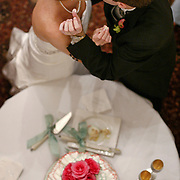 The bride and groom kiss after feeding each other during the cake cutting at a wedding reception in Beaufort. ©Travis Bell Photography