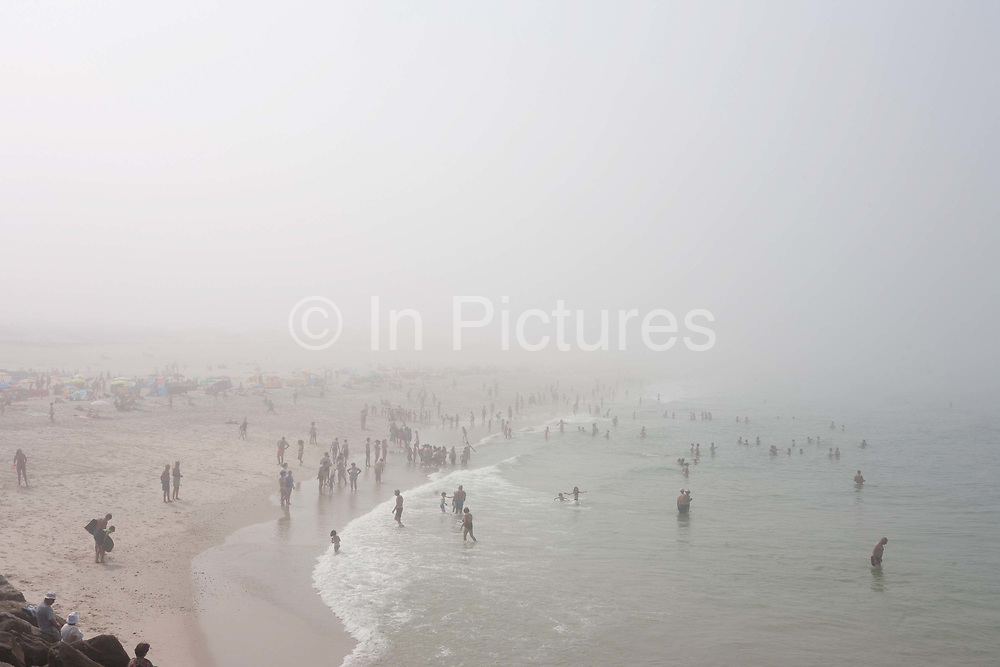 During a summer sea fog that has swept along this part of the Portuguese coast, misty sunbathers and sea swimmers enjoy cooler temperatures, on 18th July 2016, at Barra, near Aveira, Portugal. The faint figures disappear into the distance as the mist rolls across the beach.