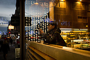 A young man in a Kimchee To Go bar sits at a high table overlooking the Strand, on 12th December 2017, in London England.