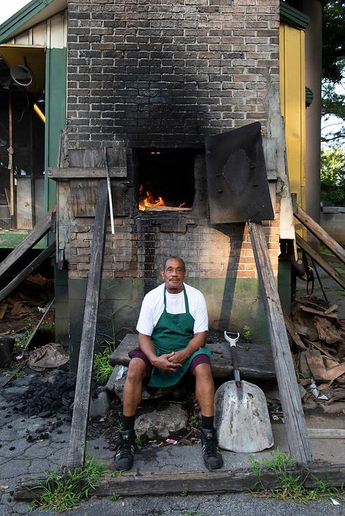 Danny Seals adds oak to the pit at Wyatt's BBQ in Atlanta, Georgia