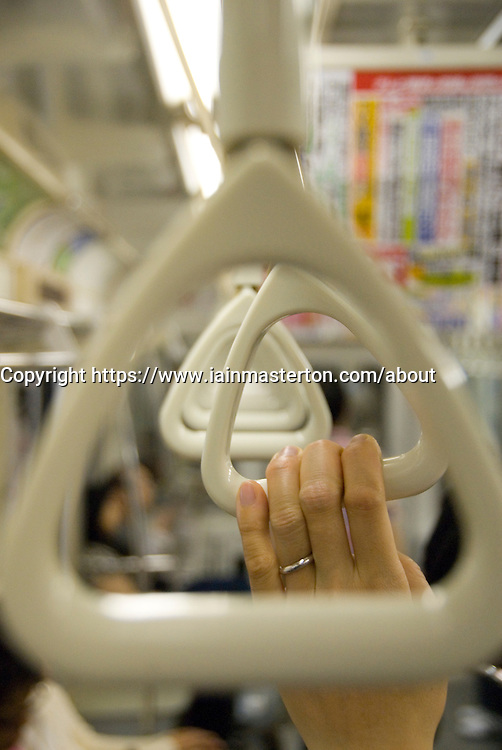 Detail of passenger holding handstrap in carriage of Tokyo subway train