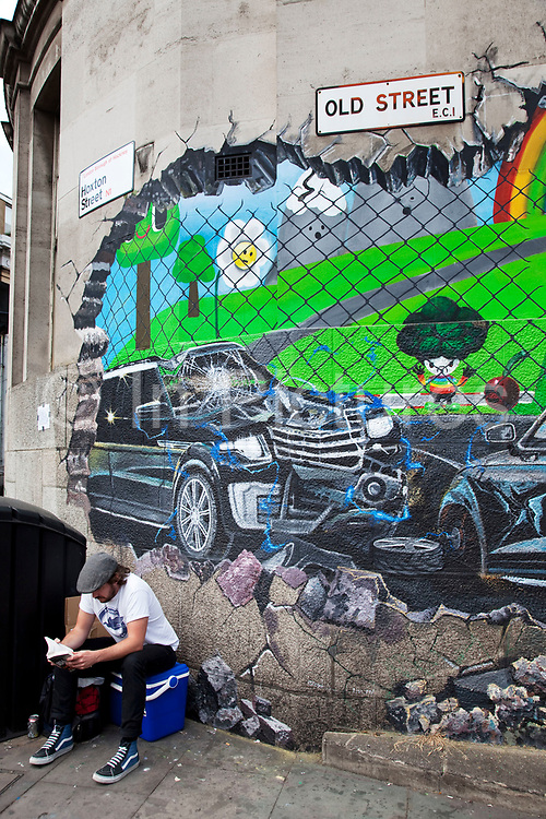 A large scale advertisement for a computer gaming system is painted onto a wall on Old Street in East London. The advert depicts two cars that have crashed through the wall. It will be up for a few days before being cleaned off.