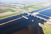 Nederland, Flevoland-Overijssel, Ramspol, 01-05-2013; nieuwe Ramspolbrug in de N50 met achter de brug de balgstuw. De vaargeul in het Ramsdiep met strekdam.<br /> Boven in beeld kassen met glastuinbouw.<br /> Ramspol, inflatable dike, between Ketelmeer and Black Water. The Balgstuw (bellow barrier) is a storm barrier and consists of an inflatable dam or dyke, composed of three bellows. Usually, each bellow rests on the bottom of the water, but now the bellows are inflated  because of maintenance.luchtfoto (toeslag op standard tarieven)<br /> aerial photo (additional fee required)<br /> copyright foto/photo Siebe Swart