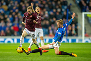 Joseph Worrall (#3) of Rangers FC slide tackles Craig Wighton (#15) of Heart of Midlothian FC during the Ladbrokes Scottish Premiership match between Rangers FC and Heart of Midlothian FC at Ibrox Stadium, Glasgow, Scotland on 3 April 2019.