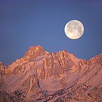 The moon sets at sunrise over Mount Humphreys on the Sierra Nevada crest above Bishop, California.