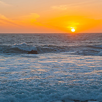 The sun sets over waves at Panther Beach, north of Santa Cruz, California