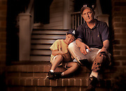 An older man sits with his grandson on their front porch, getting ready to play baseball