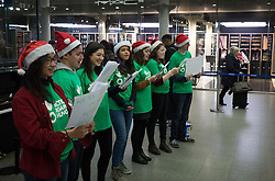 © Licensed to London News Pictures. 23/12/2016. London, UK. A charity choir sing carols for passengers at St Pancras Eurostar terminal. The Christmas getaway begins today with stations, airports and roads expected to be very busy as people start their Christmas holidays. Photo credit: Peter Macdiarmid/LNP