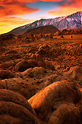 Rocks and boulders in California's Alabama HIlls at sunrise, with the Sierra Nevada range as backdrop.