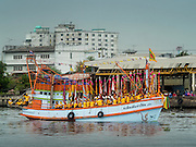 """23 JUNE 2015 - MAHACHAI, SAMUT SAKHON, THAILAND:  Attendants of the City Pillar Shrine on a fishing boat goes up the Tha Chin (Chin River) during the City Pillar Shrine procession in Mahachai. The Chaopho Lak Mueang Procession (City Pillar Shrine Procession) is a religious festival that takes place in June in front of city hall in Mahachai. The """"Chaopho Lak Mueang"""" is  placed on a fishing boat and taken across the Tha Chin River from Talat Maha Chai to Tha Chalom in the area of Wat Suwannaram and then paraded through the community before returning to the temple in Mahachai.   PHOTO BY JACK KURTZ"""