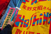 Campaigners carry flags calling for the release of jailed activist, Fumiaki Hoshino who was arrested in 1975 for the alleged killing of a police officer during riots in Tokyo and sentenced to life imprisonment, at an anti-war and left wing demonstration in Shibuya, Tokyo, Japan Saturday March 20th 2010