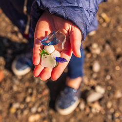 A girl shows off a handful of sea glass in Lubec, Maine.