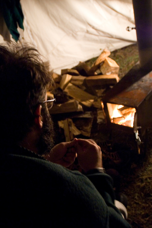 Hunters relax and warm up in front of a woodstove in a canvas tent on a hunting trip near Gwinn Michigan.