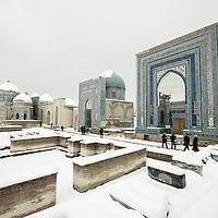 """USE ARROWS ← → on your keyboard to navigate this slide-show<br /> <br /> Samarkand, Uzbekistan 19 March 2012<br /> View of a snow-covered Shah-i-Zinda necropolis.<br /> The Shah-i-Zinda Ensemble includes mausoleums and other ritual buildings of 9-14th and 19th centuries. <br /> The name Shah-i-Zinda (meaning """"The living king"""") is connected with the legend that Kusam ibn Abbas, the cousin of the prophet Muhammad was buried there. <br /> He came to Samarkand with the Arab invasion in the 7th century to preach Islam. Popular legends speak that he was beheaded for his faith. But he took his head and went into the Garden of Paradise, where he's still living now.<br /> Photo: Ezequiel Scagnetti"""