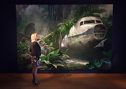 © Licensed to London News Pictures. 05/10/2012. LONDON, UK. A member of Christie's staff looks at Jonathan Wateridge's 'Jungle Scene With Plane Wreck' (2007) a 2.72 x 4 metre painting estimated to fetch GB£100,000-150,000 at an auction preview in London today (05/10/12). The evening auction, consisting of post-war and contemporary art, takes place at Christie's St James' auction house on the 11 October 2012. Photo credit: Matt Cetti-Roberts/LNP