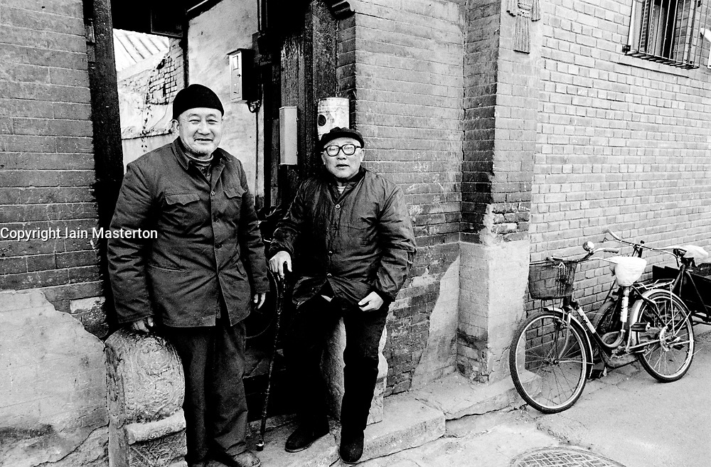 Elderly men outside house in a Beijing hutong in China