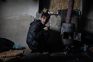 A man from Afghanistan is seen smoking a cigaret next to a stove. Many are living in abandoned building around the town of Bihac, waiting to attempt to cross the Bosnian Croatian border, Bihac January 27, 2021.