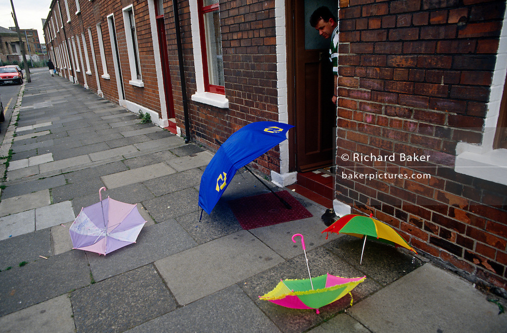 A father looks down at four coloured umbrellas that have been left on the pavement outside a terraced street in Belfast.