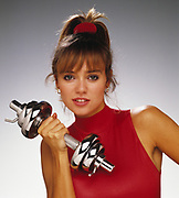 Beautiful woman flexing silver dumbbell  and wearing red turtleneck top. Photo against glowing gray background