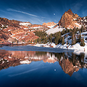 Lake Blanche, during spring in the Wasatch, reflects the jagged Sundial Peak.