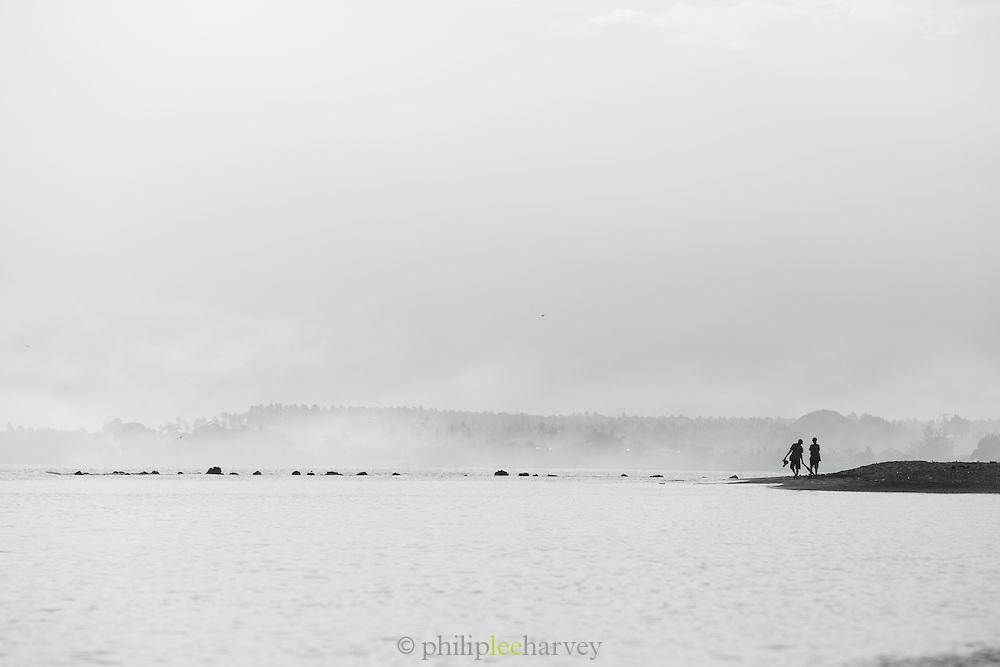 people walk along the coast near Kokopo Beach Bungalo Resort,  East New Britain, Papua New Guinea