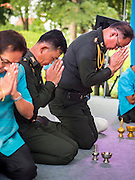 11 AUGUST 2015 - BANGKOK, THAILAND: Police officers pray while making an offering to Buddhist monks during a service to honor Queen Sirikit of Thailand before her 83rd birthday. Queen Sirikit was born Mom Rajawongse Sirikit Kitiyakara on August 12, 1932. She is the queen consort of Bhumibol Adulyadej, King (Rama IX) of Thailand. She met Bhumibol in Paris, where her father was the Thai ambassador. They married in 1950, she was appointed Queen Regent in 1956. The King and Queen had one son and three daughters. She has not made any public appearances since her hospitalization in 2012. Her birthday is celebrated as Mother's Day in Thailand, schools and temples across Thailand hold ceremonies to honor the Queen and mothers.       PHOTO BY JACK KURTZ
