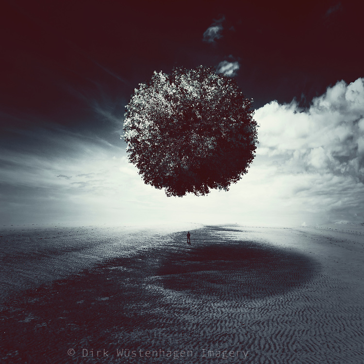 Planet composed of trees hovering over a desolate plain with a man standing in the shadow.
