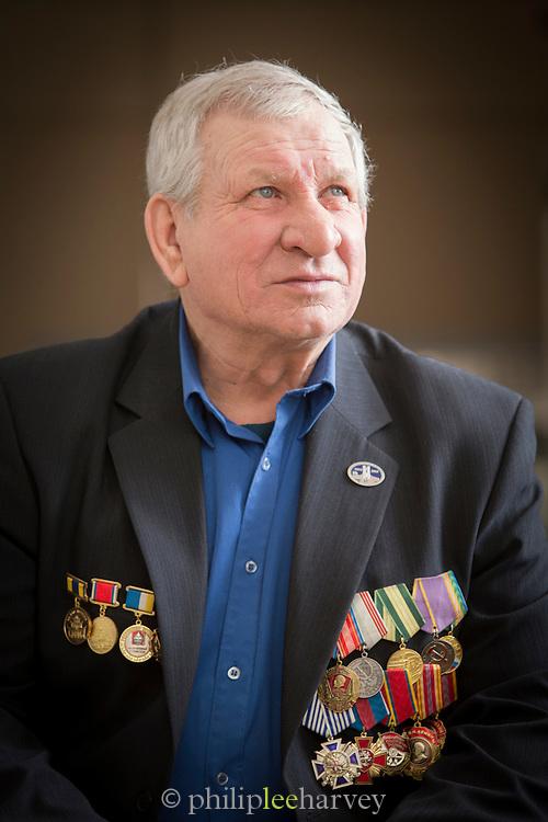 Veteran Albert Ivanovich with medals at the BAM (Baikal-Amur Mainline) railway museum, Severobaikalsk. Siberia, Russia