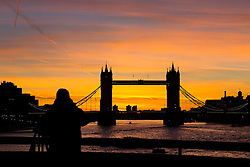 © Licensed to London News Pictures. 25/01/2016. London, UK. Colourful sky behind Tower Bridge just ahead of sunrise and mild weather this morning.  Photo credit : Vickie Flores/LNP