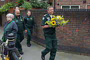 NHS ambulance staff carry flowers while attending the memorial service on the first anniversary of the Grenfell tower block disaster, on 14th June 2018, in London, England. 72 people died when the tower block in the borough of Kensington & Chelsea were killed in what has been called the largest fire since WW2. The 24-storey Grenfell Tower block of public housing flats in North Kensington, West London, United Kingdom. It caused 72 deaths, out of the 293 people in the building, including 2 who escaped and died in hospital. Over 70 were injured and left traumatised. A 72-second national silence was held at midday, also observed across the country, including at government buildings, Parliament.