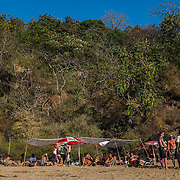 A group of foreign tourists enjoy an afternoon picnic party on Butterfly beach, some 20 minutes by boat south of Agonda beach. A boat is like a taxi on Agonda beach, and many poeple use the boats for dolphine viewing trips, or short excursions to the nearby smaller and more secluded beaches like Honeymoon beach, or Butterfly beach.