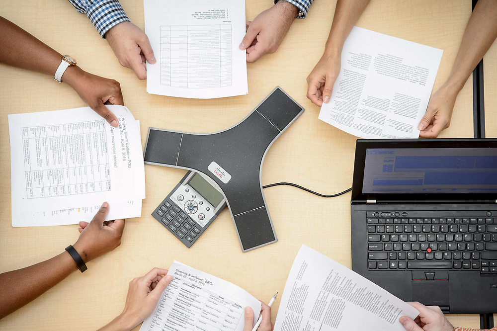 Image of workers arms sitting around a table on a conference call.