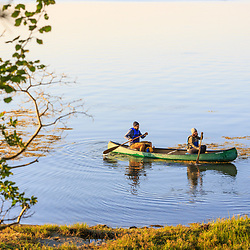 A couple and their young daughter canoeing after a night of camping on Lanes Island in Casco Bay. Yarmouth, Maine.