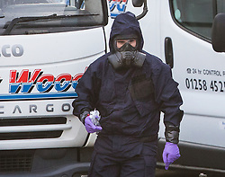 © Licensed to London News Pictures. 15/03/2018. Alderholt, UK. A policeman in protective overalls and a gas mask works at Ashley Wood Recovery in Salisbury where former Russian spy Sergei Skripal and his daughter Yulia were poisoned with nerve agent. The couple where found unconscious on bench in Salisbury shopping centre. A policeman who went to their aid is currently recovering in hospital. Photo credit: Peter Macdiarmid/LNP