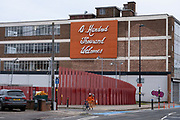 Woman wearing an orange coat matching the sign passes the One Hundred Thousand Welcomes sign near Digbeth Coach Station in the City Centre on 18th January 2020 in Birmingham, United Kingdom.