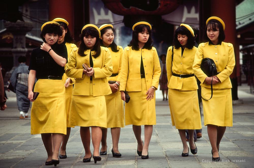 Group of tour guides in uniform walking at Asakusa Kannon Temple, Asakusa district, Tokyo, Japan