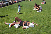 A woman, clearly inebriated, draws no attention as she hikes up her clothes to sunbathe while sound asleep. Pike Place Market park, Seattle.