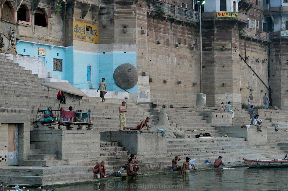 Early morning bathing and exercise overlooking the river Ganga. Near the Dashashwamedh ghat. Colorful and popular Dasasvamedha Ghat gets a lot of attention from religious pilgrims, locals, and tourists alike and is one of the busiest bathing ghats in the city of Varanasi.